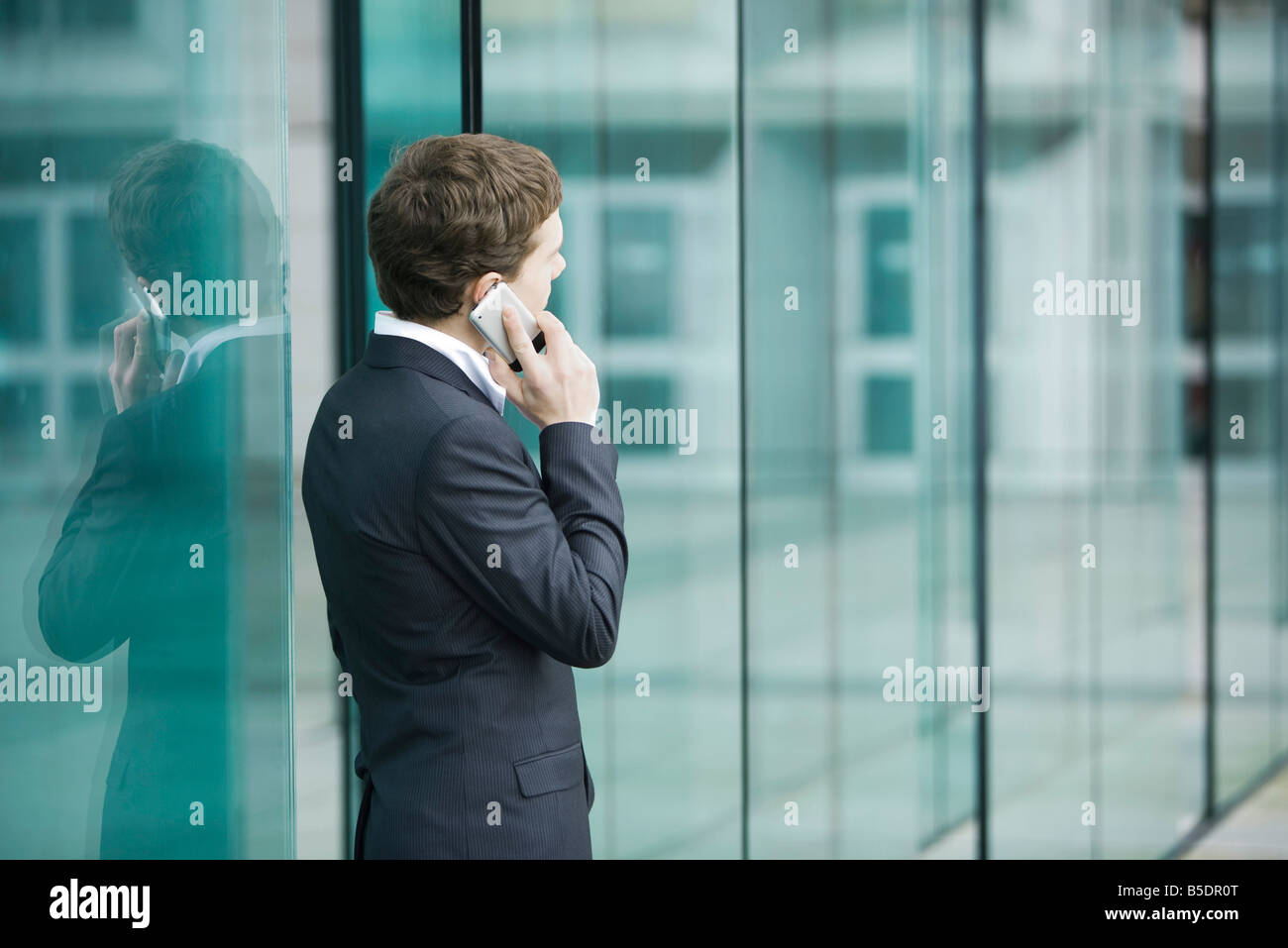 Young businessman standing outside sliding glass doors talking on cell phone - Stock Image