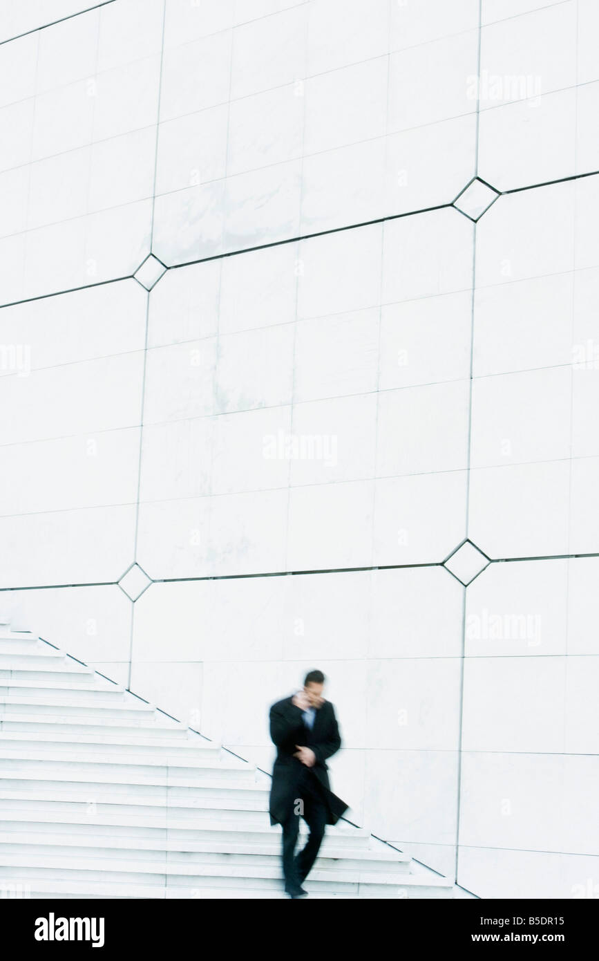 Businessman descending outdoor stairs, talking on cell phone, holding coat closed against the wind - Stock Image