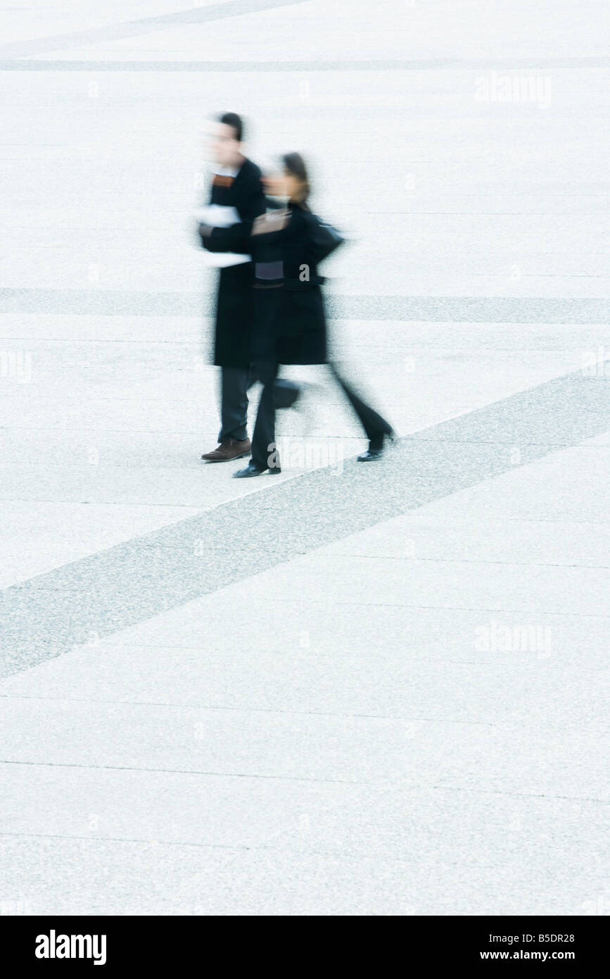Businessman and businesswoman walking together across public square - Stock Image