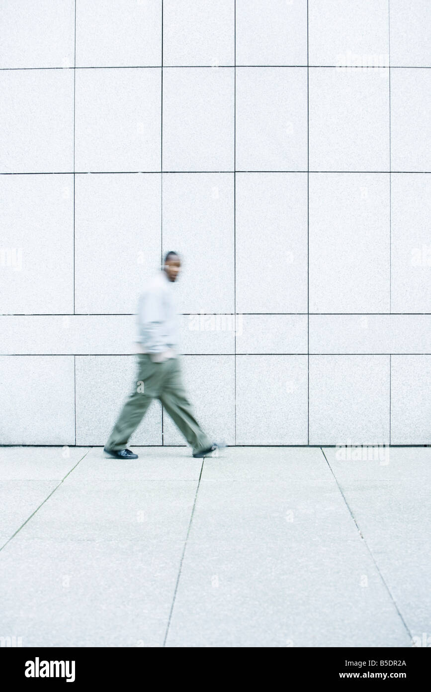 Man walking with hands in his pockets down sidewalk Stock Photo