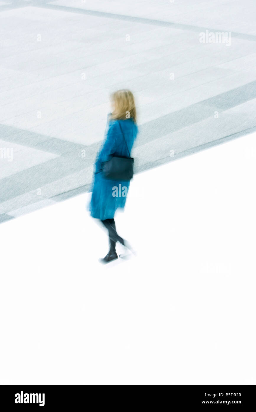 Woman in blue overcoat descending stairs - Stock Image