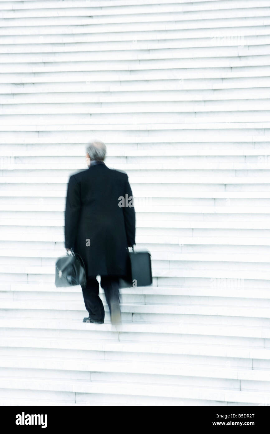 Businessman carrying two heavy bags slowly going up stairs outdoors - Stock Image