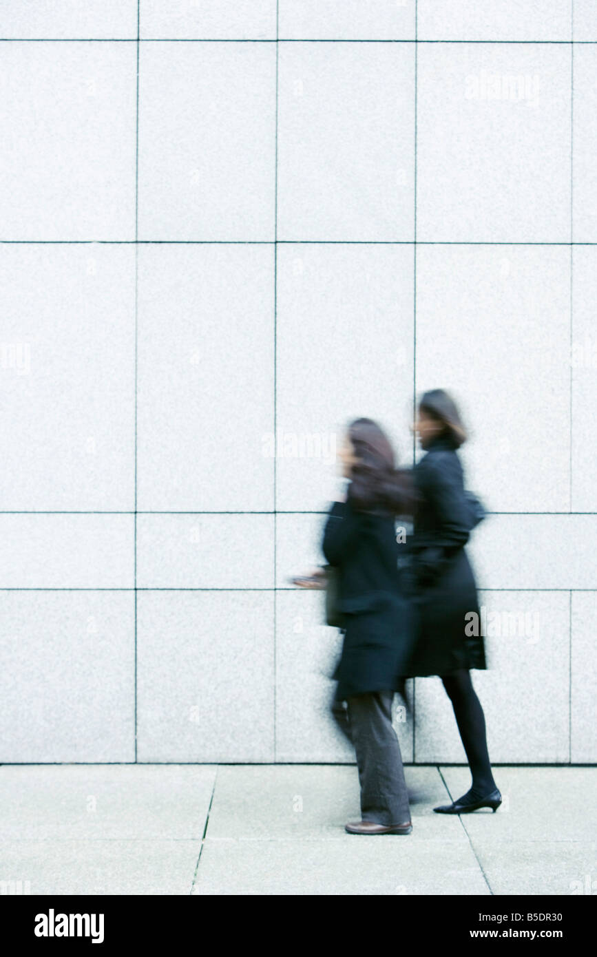 Two businesswomen walking side by side down sidewalk - Stock Image