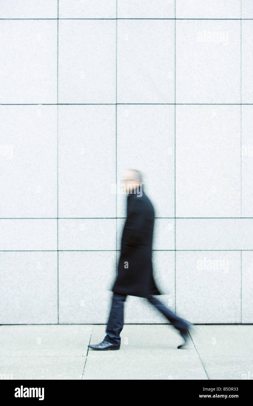 Businessman walking alone hands in pockets down sidewalk - Stock Image