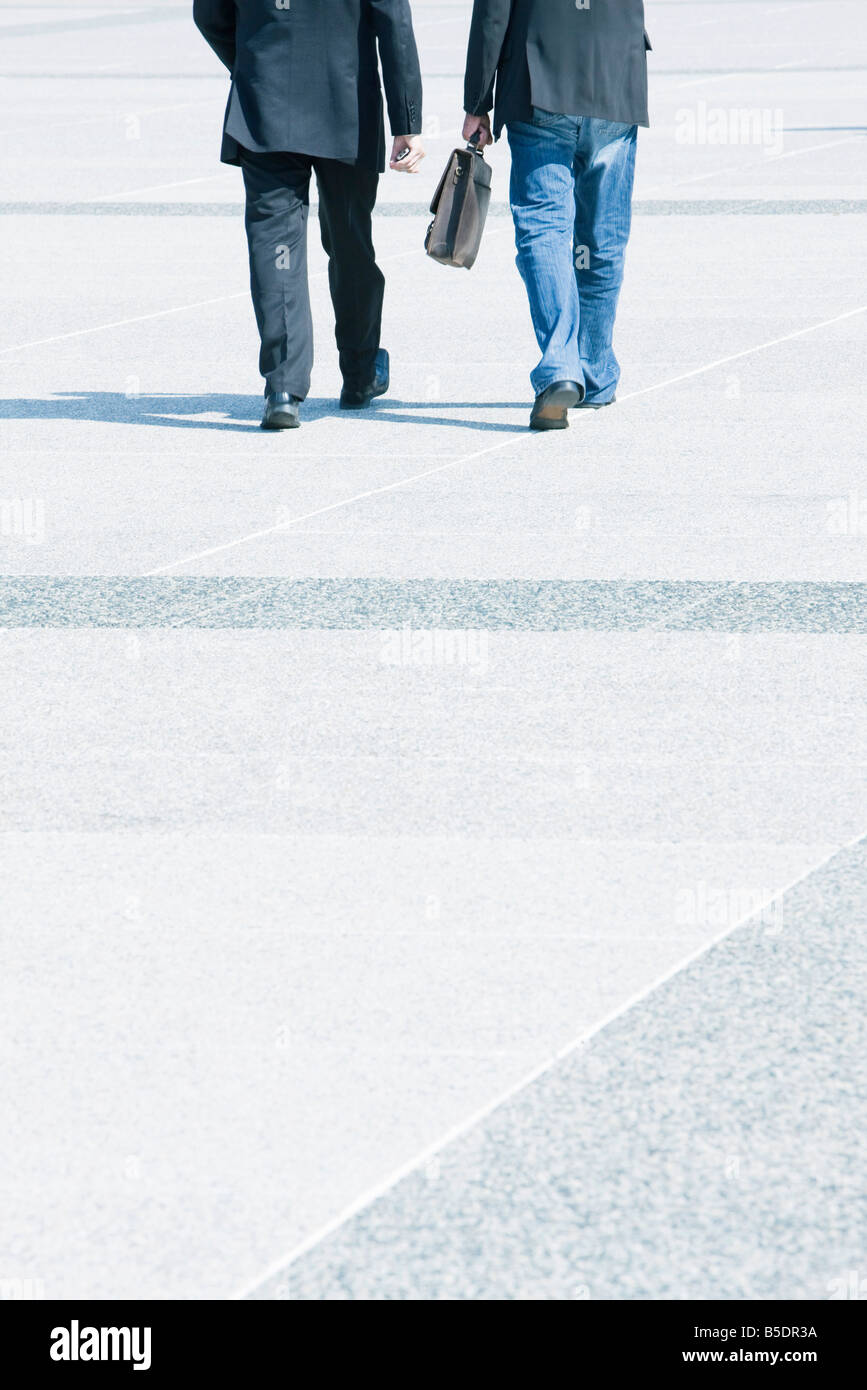 Two businessmen walking together wearing business attire, one wearing jeans with blazer - Stock Image