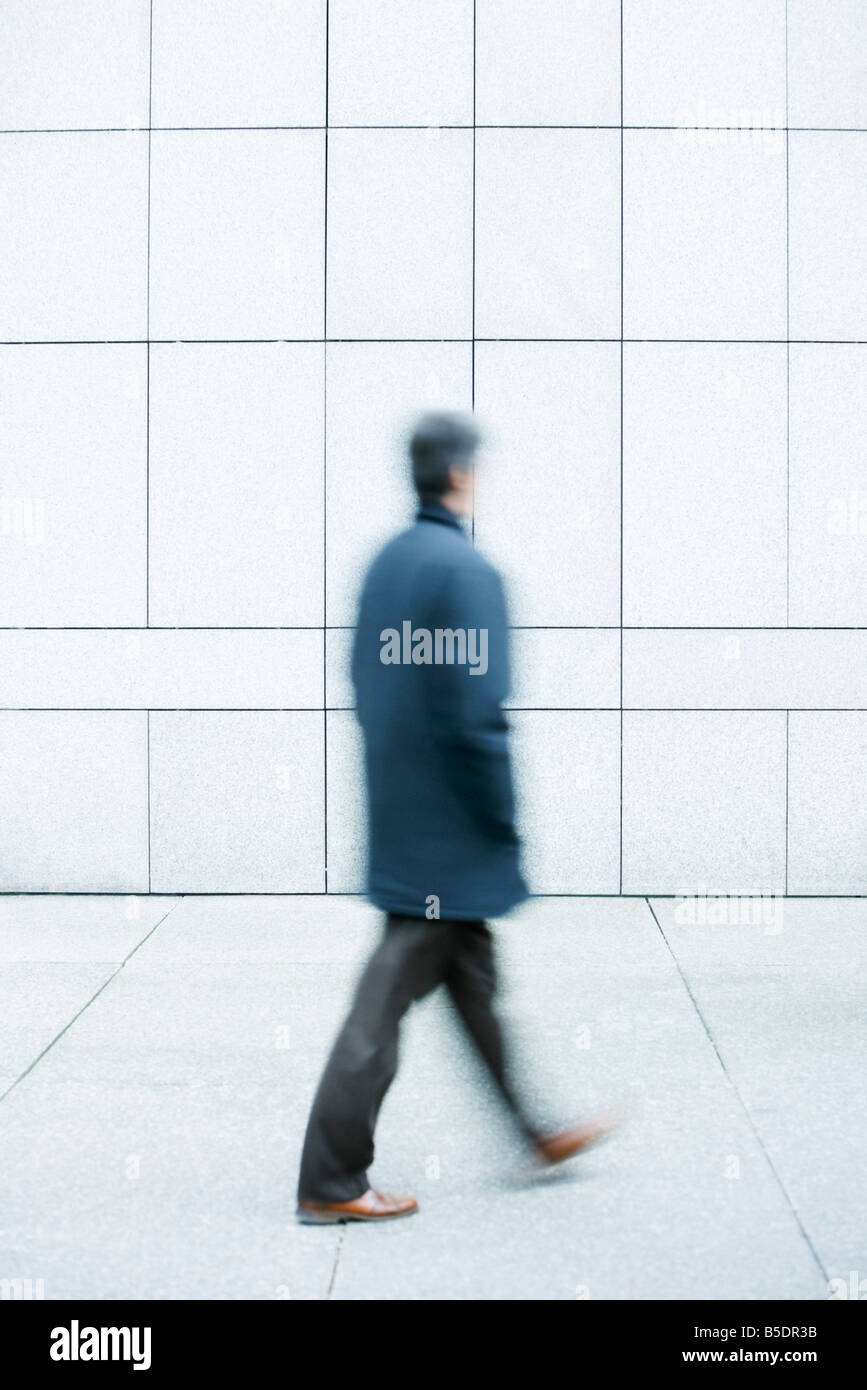 Man walking with hands in pockets down sidewalk - Stock Image