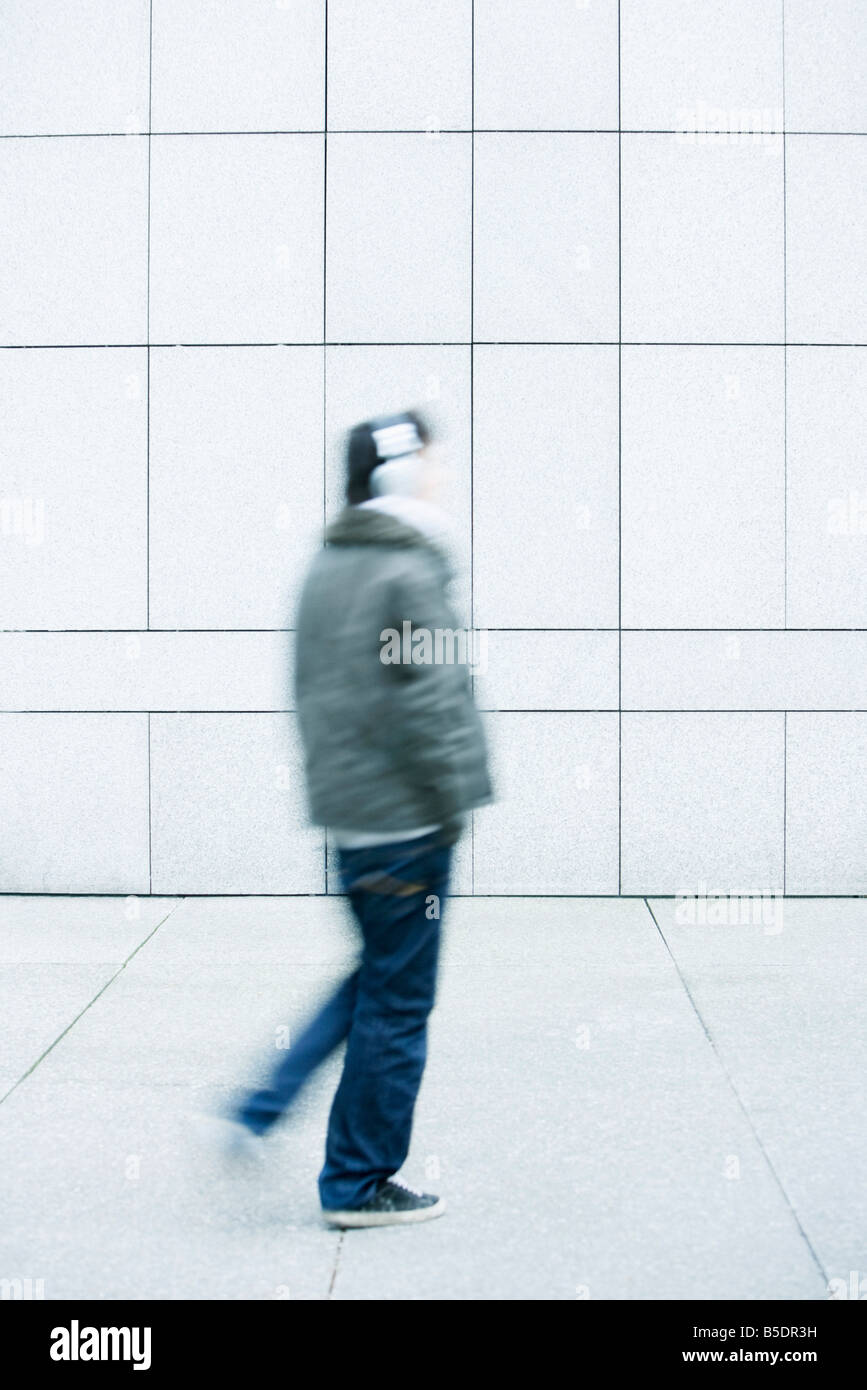 Man walking with hands in pockets on sidewalk - Stock Image