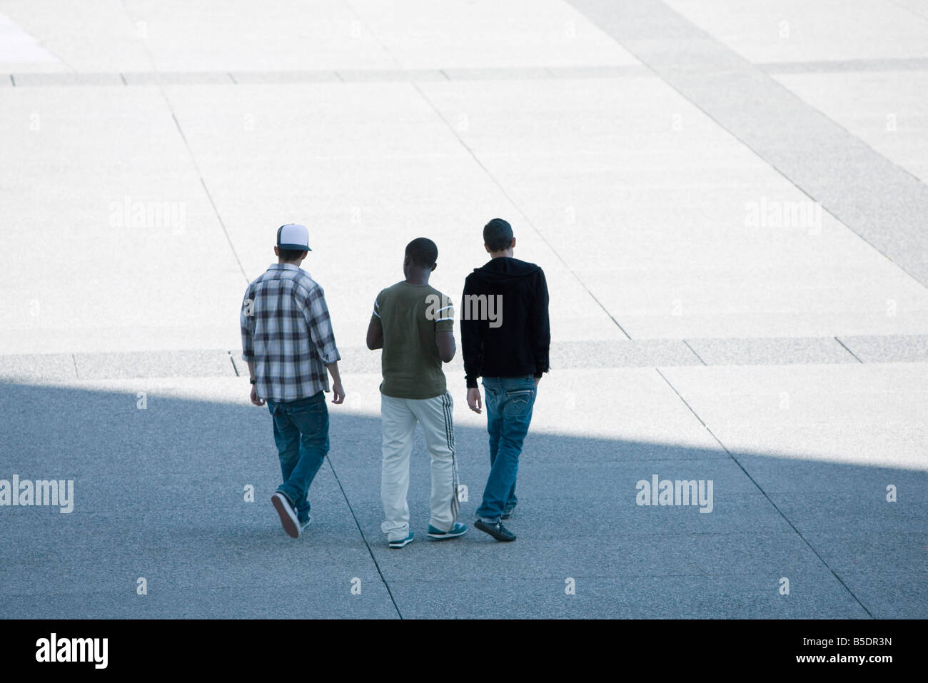 Three young men walking together across public square - Stock Image