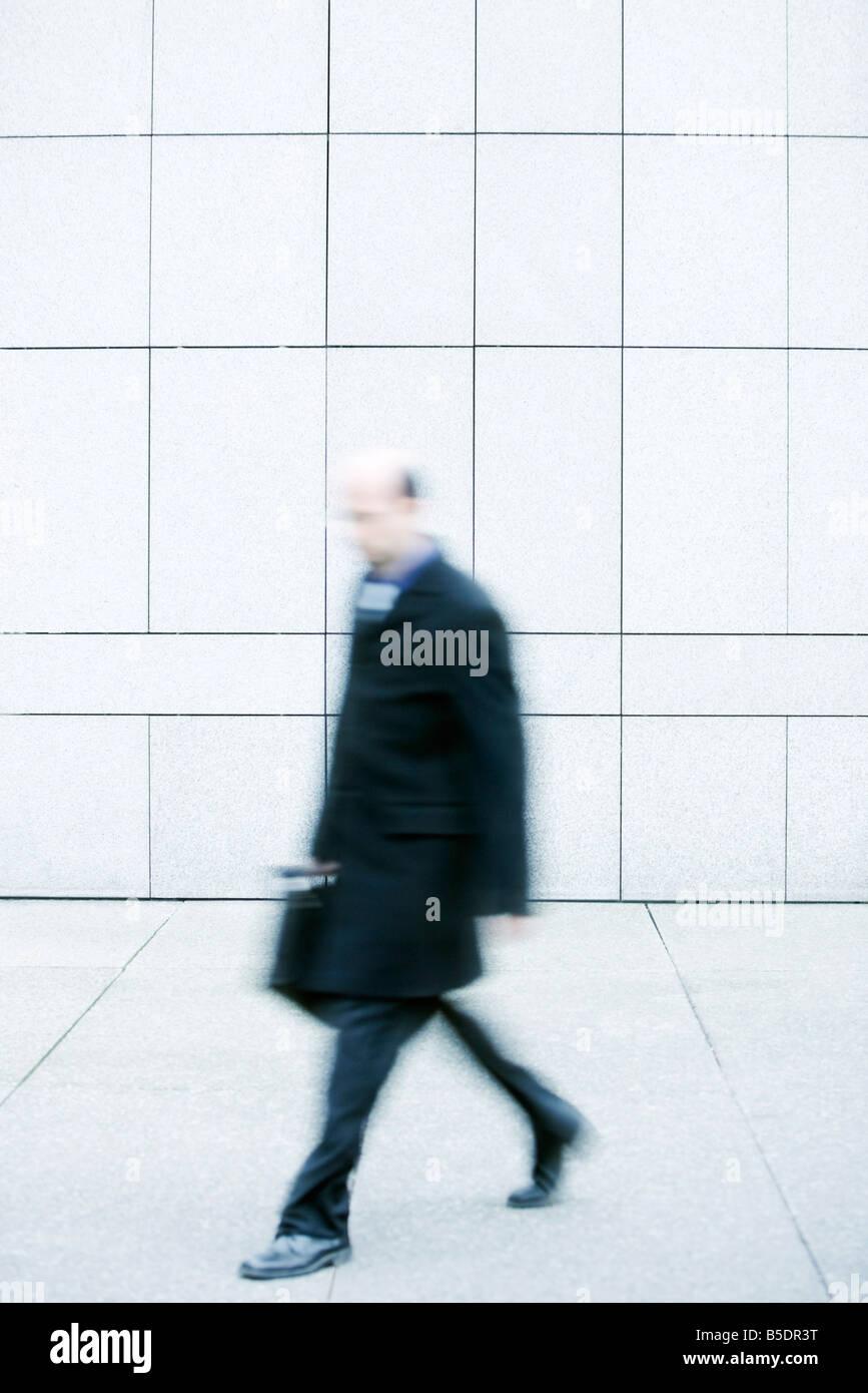 Businessman walking on sidewalk - Stock Image