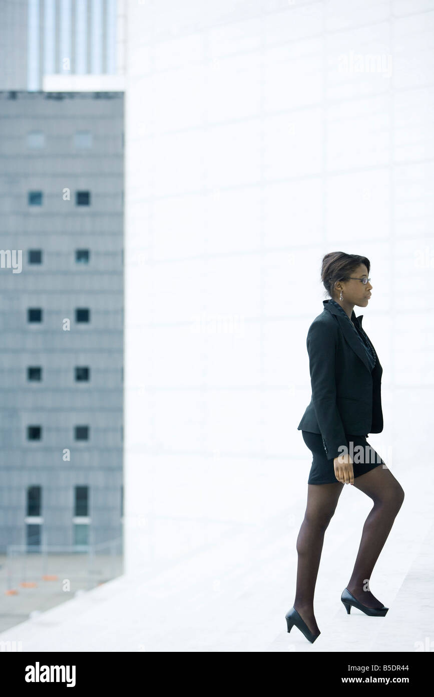 Businesswoman walking up steps - Stock Image