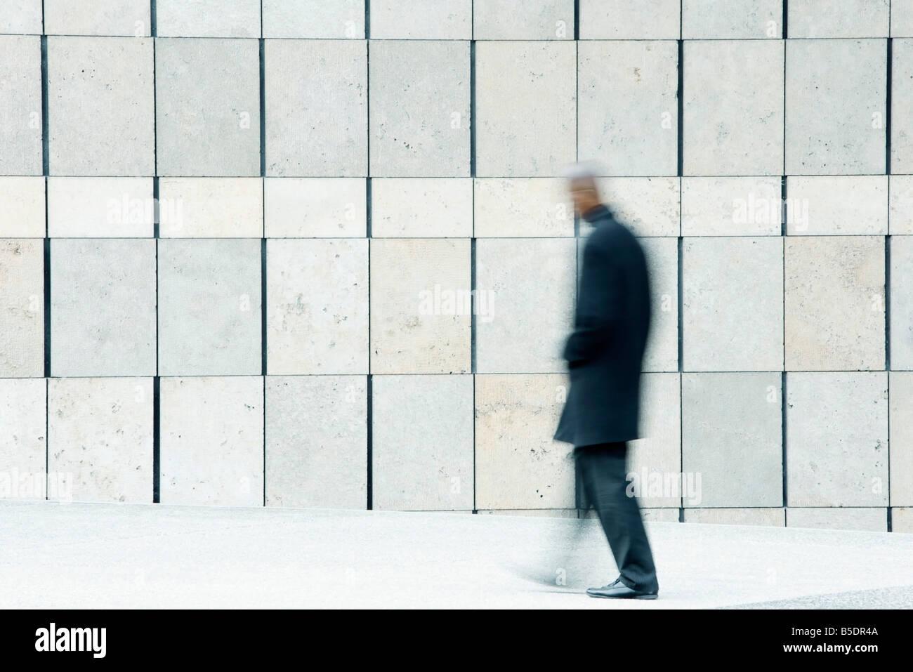 Man walking on sidewalk - Stock Image