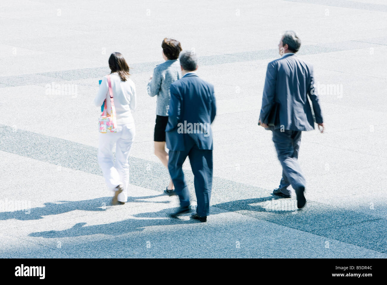Pedestrians walking across public square - Stock Image