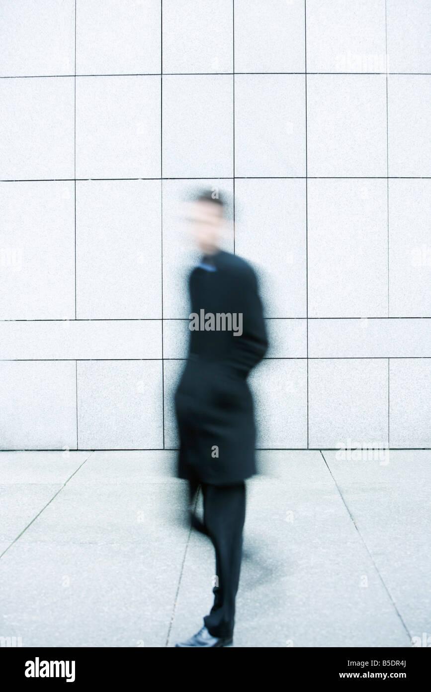 Businessman hurrying down sidewalk - Stock Image