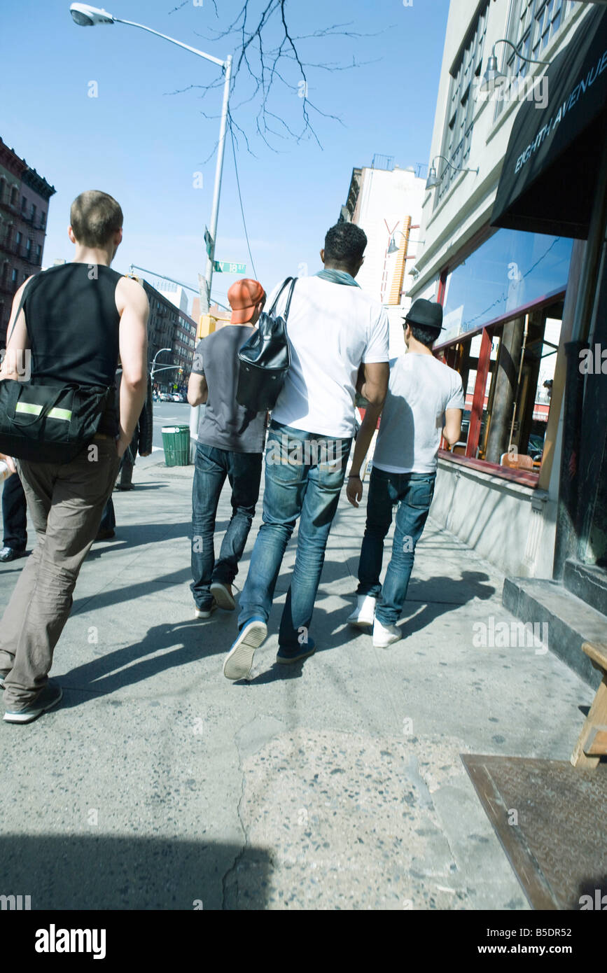 Young men walking NE along sidewalk on 8th Avenue in Chelsea, New York City, rear view - Stock Image