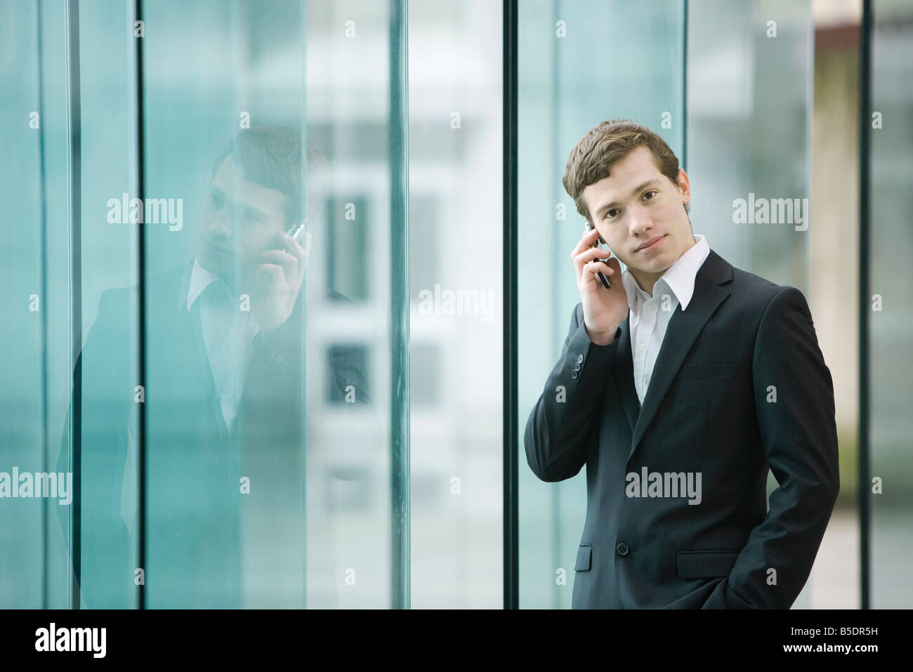 Businessman standing by glass wall talking on cell phone - Stock Image