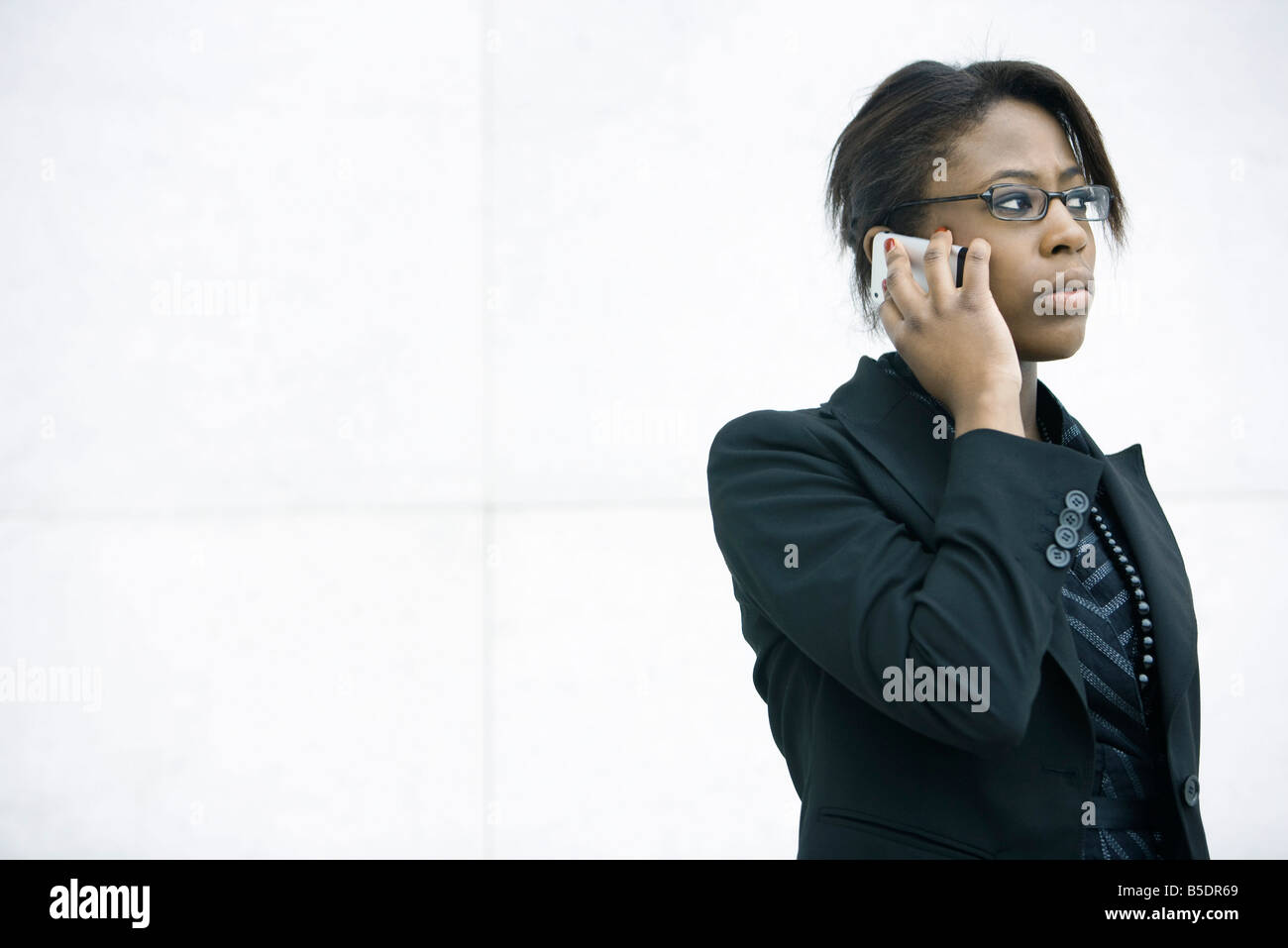 Businesswoman using cell phone, looking away - Stock Image