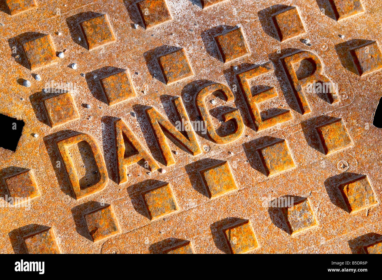 rusted man hole sewer cover reading Danger - Stock Image