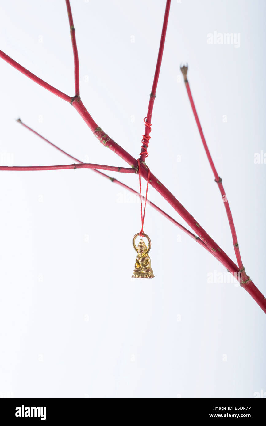 Miniature Buddha ornament hanging from bare branch - Stock Image