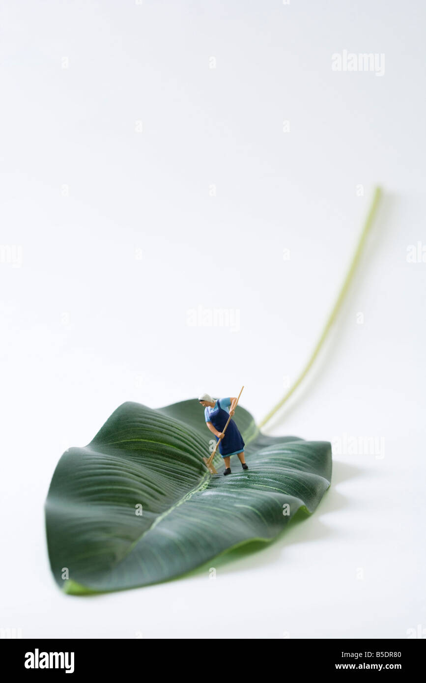 Miniature cleaning lady sweeping leaf - Stock Image