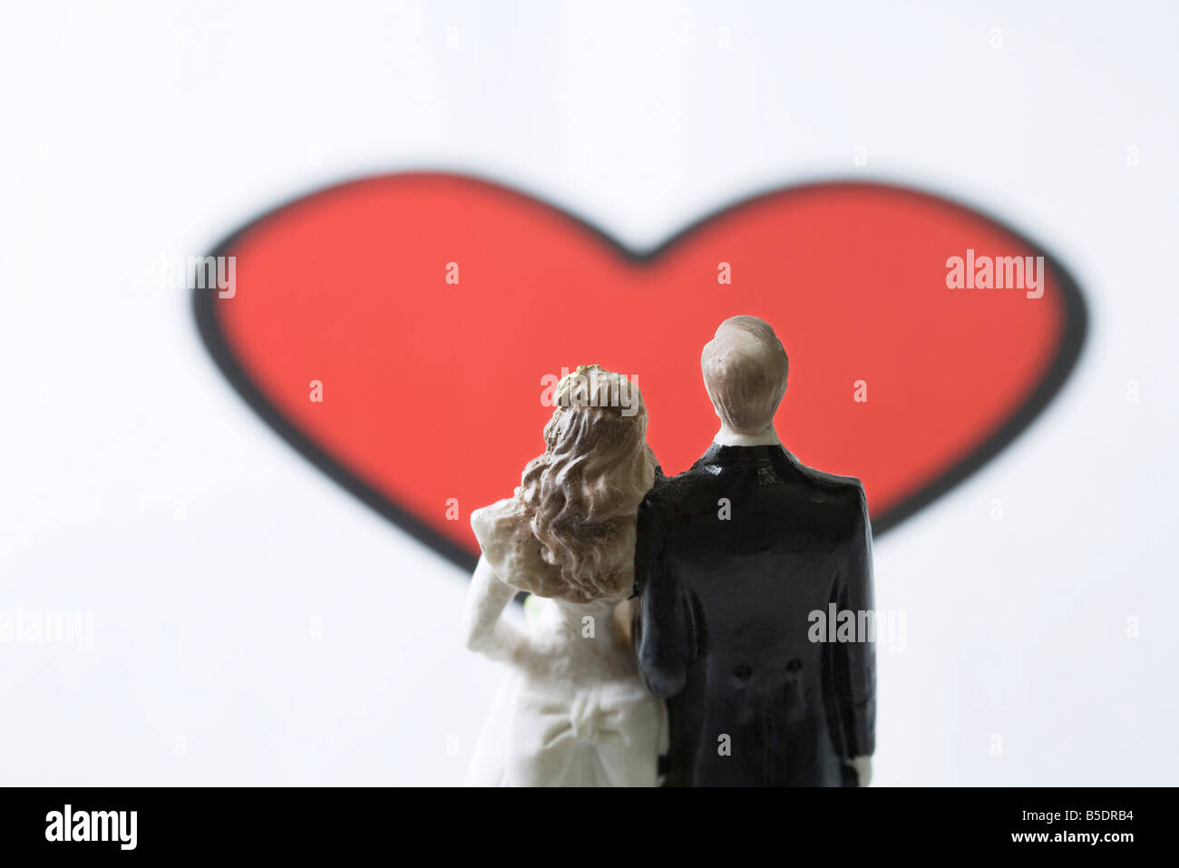 Miniature bride and groom standing in front of large heart graphic - Stock Image
