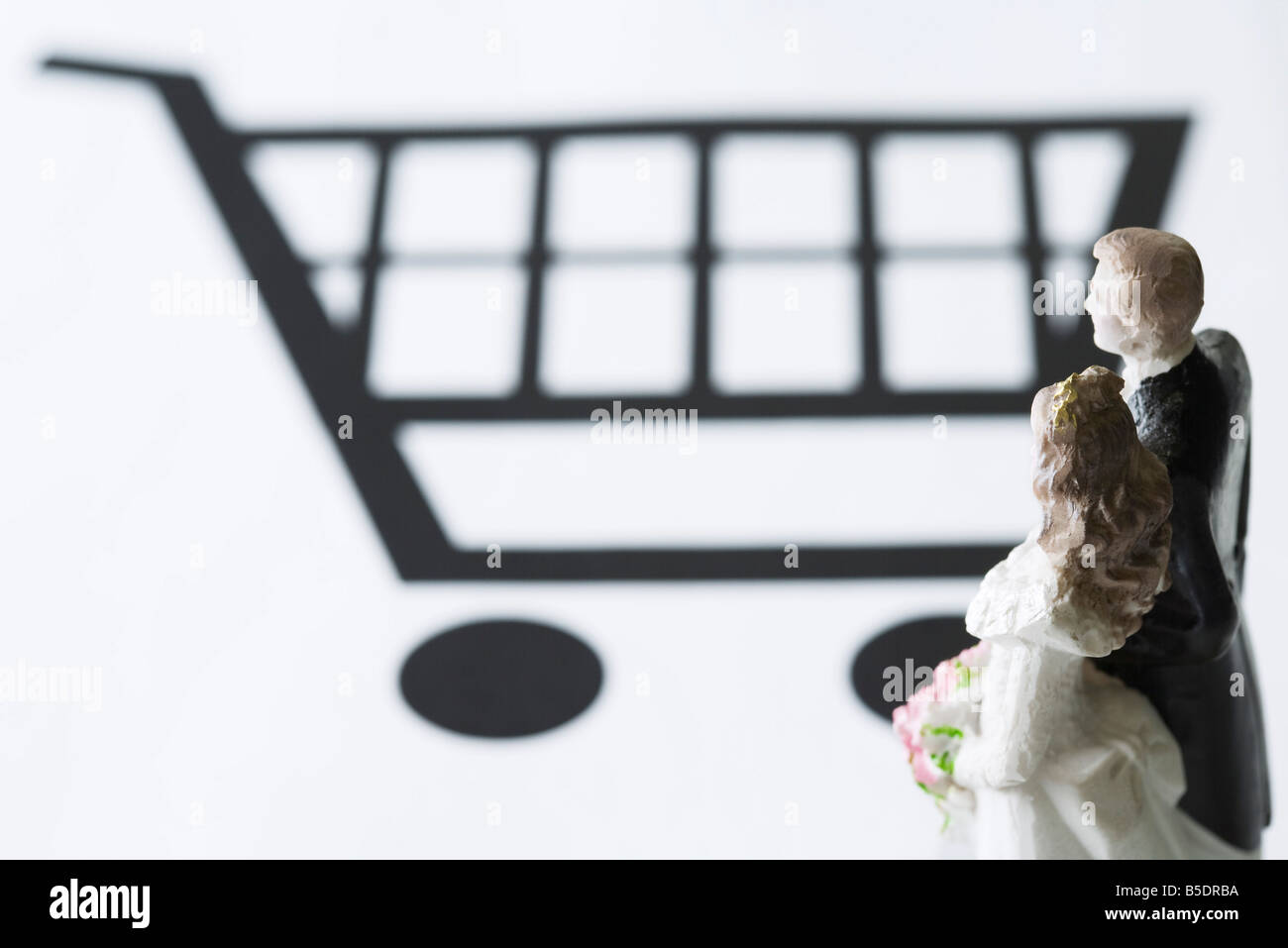 Bride and groom figures looking at shopping cart - Stock Image