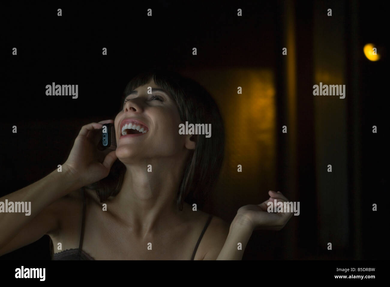 Woman talking on cell phone in darkly lit room, head back, laughing - Stock Image