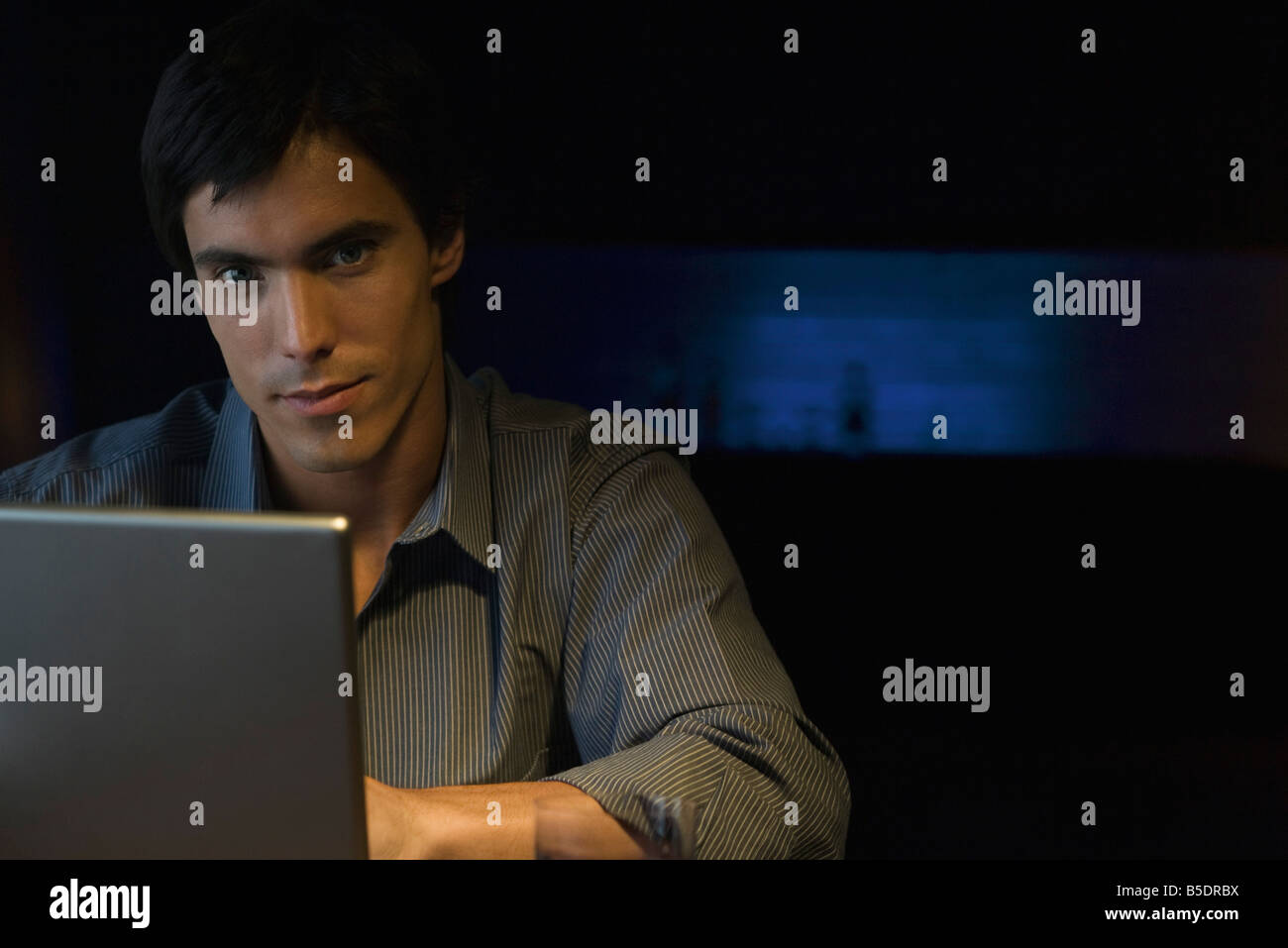 Man sitting in darkly lit room at table with laptop, looking at camera, portrait - Stock Image