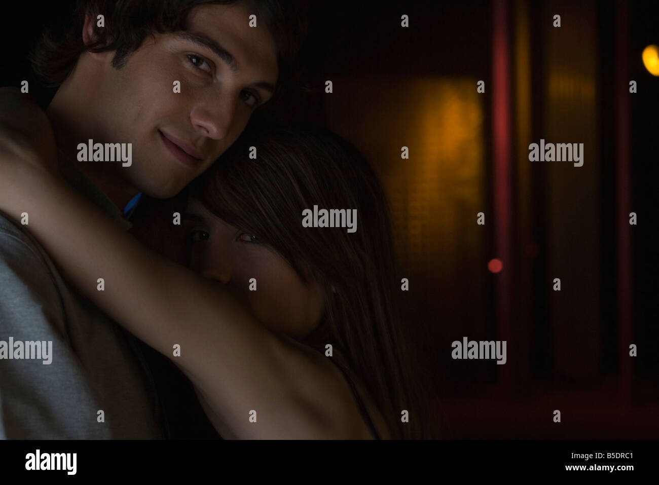 Couple embracing in darkly lit room, looking over shoulder at camera - Stock Image