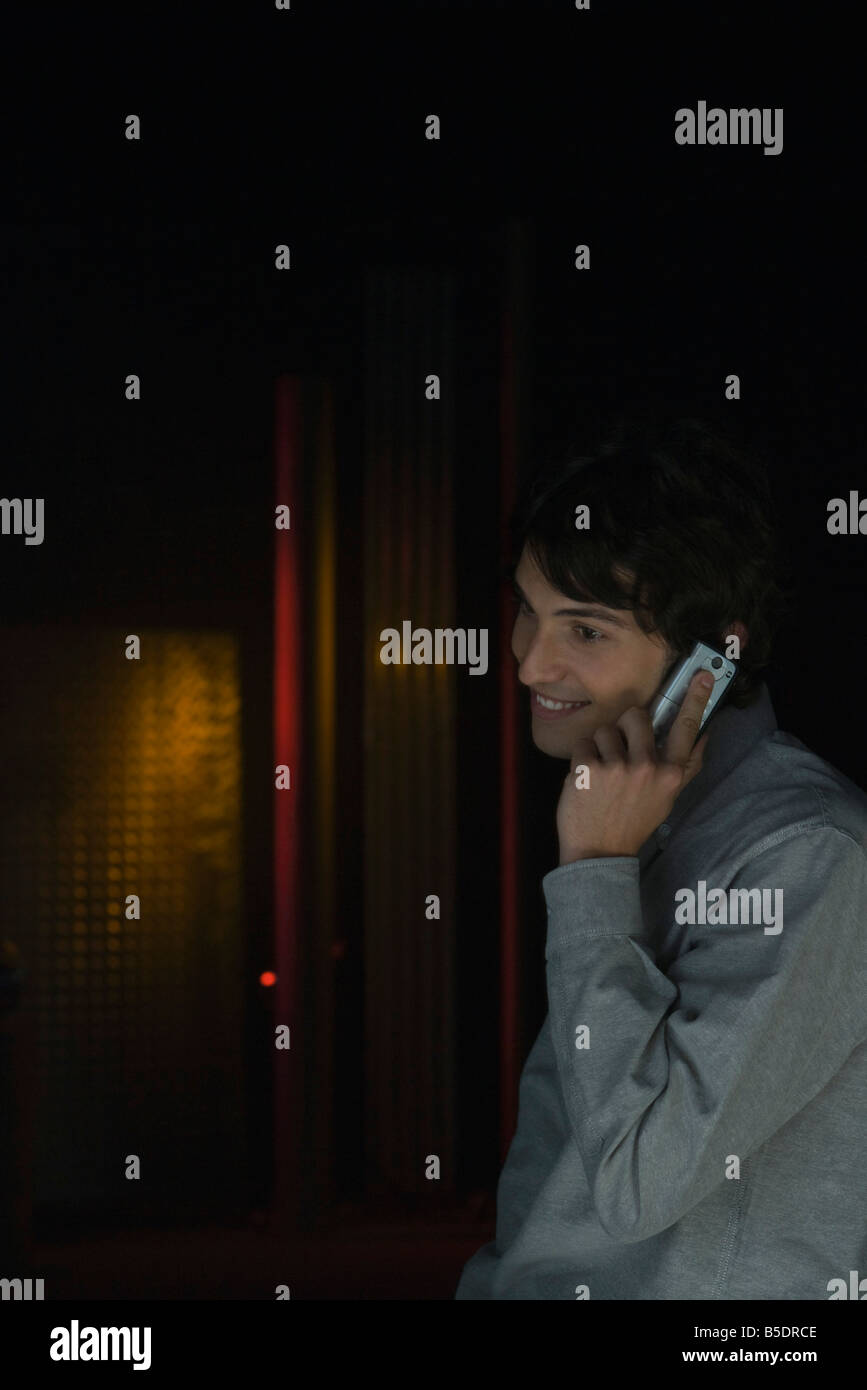 Man in darkly lit room using cell phone, listening, smiling, looking away - Stock Image
