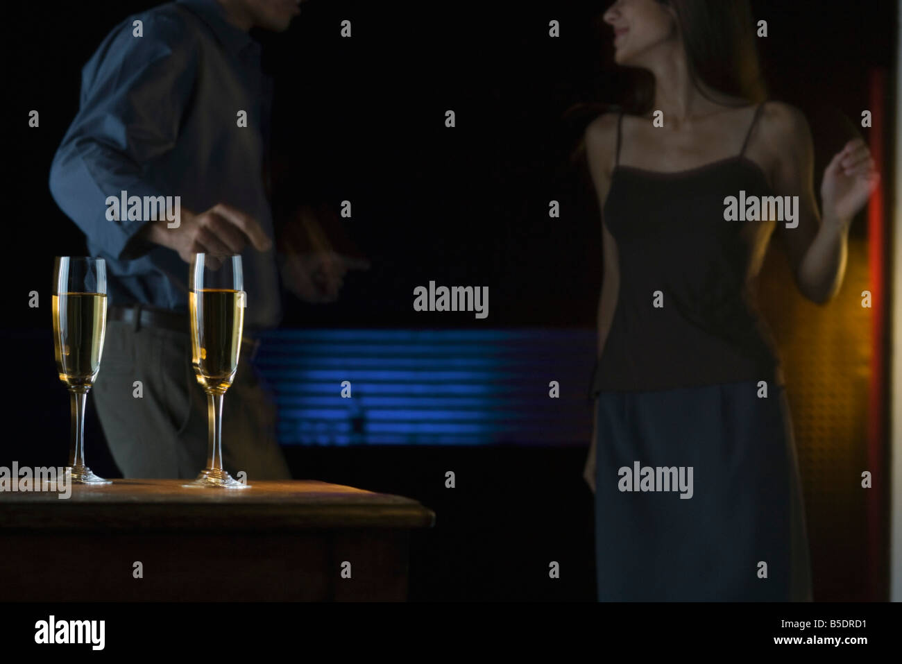 Glasses of champagne, couple dancing in darkly lit background - Stock Image