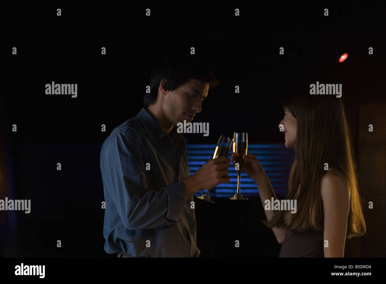 Couple clinking glasses in darkly lit room, smiling - Stock Image
