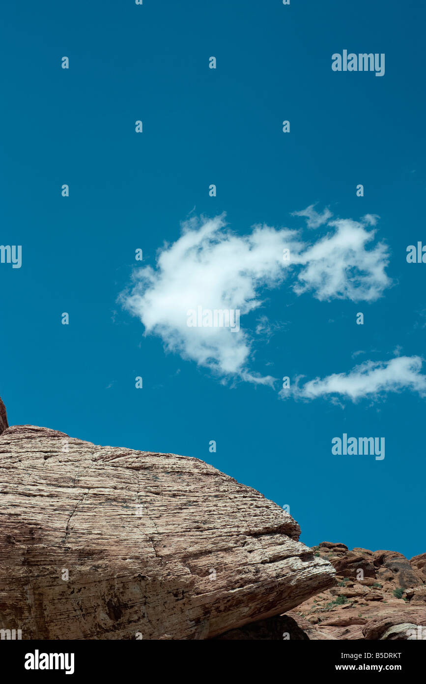 Rocky outcropping, single wispy cloud in sky, low angle view Stock Photo