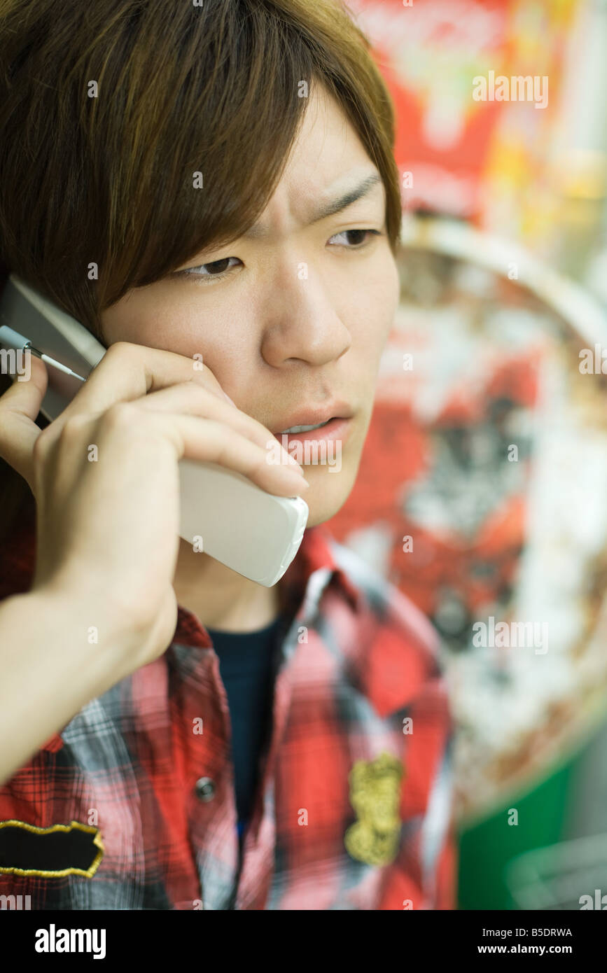 Young man talking on cell phone, furrowing brow - Stock Image