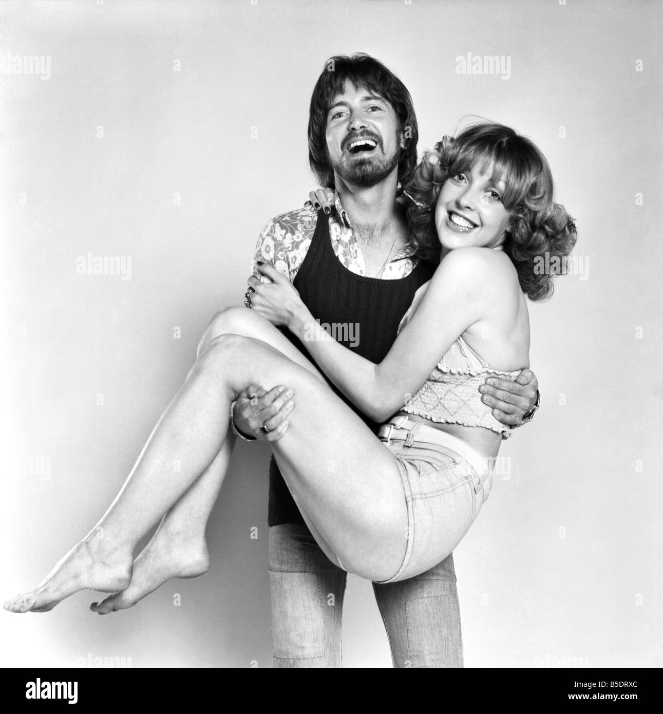 Couple wearing 1970s fashion. The woman wearing a matching top and hot pants with the man wearing a floral patterned - Stock Image
