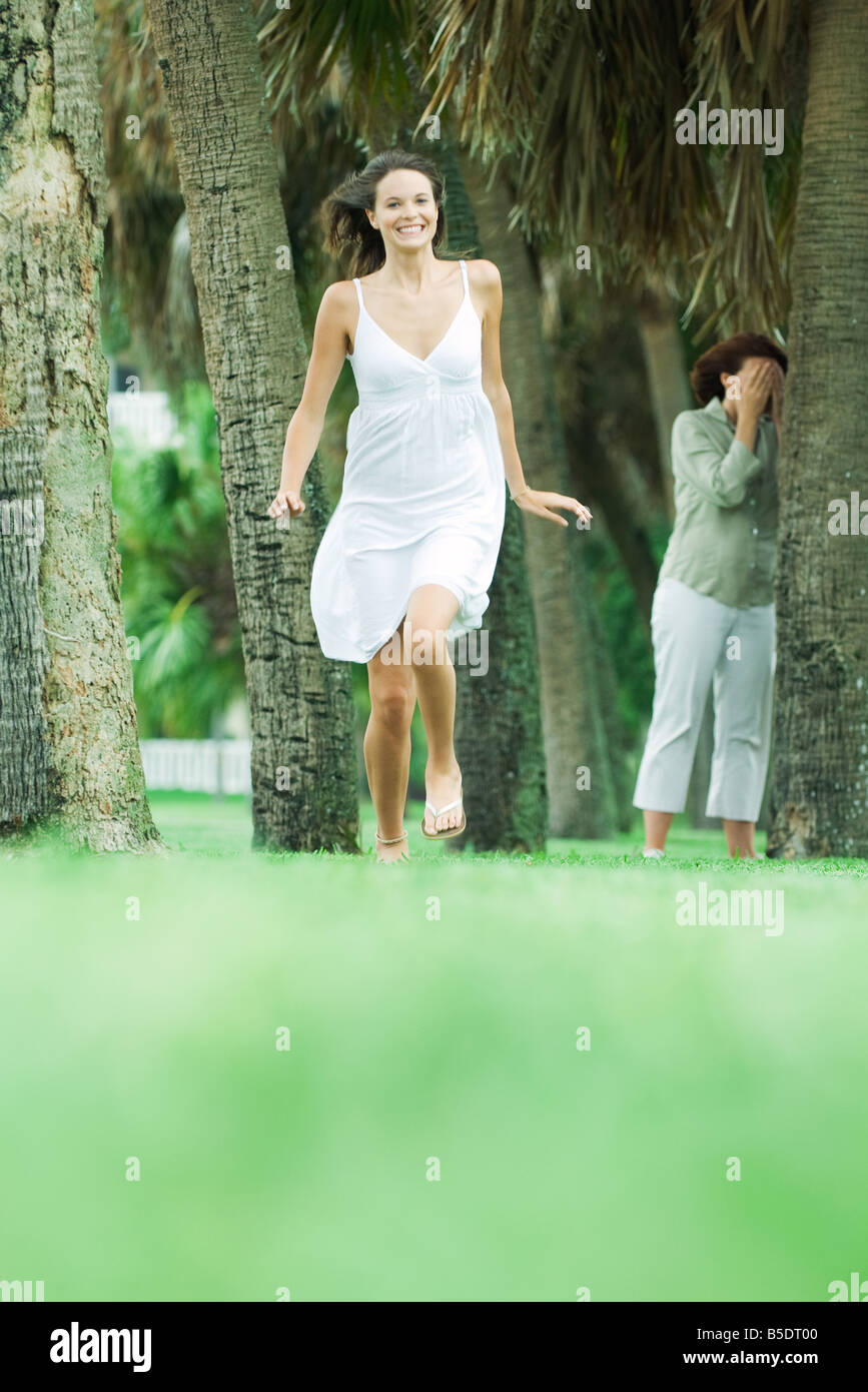 Mother and teen daughter playing hide-and-seek in park, girl running toward camera Stock Photo