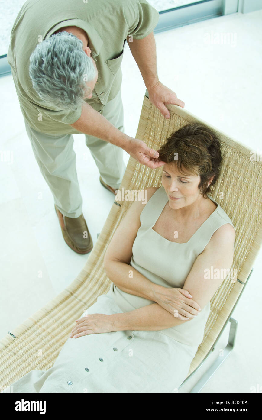 Woman relaxing on lounge chair, husband bending over to touch her hair - Stock Image