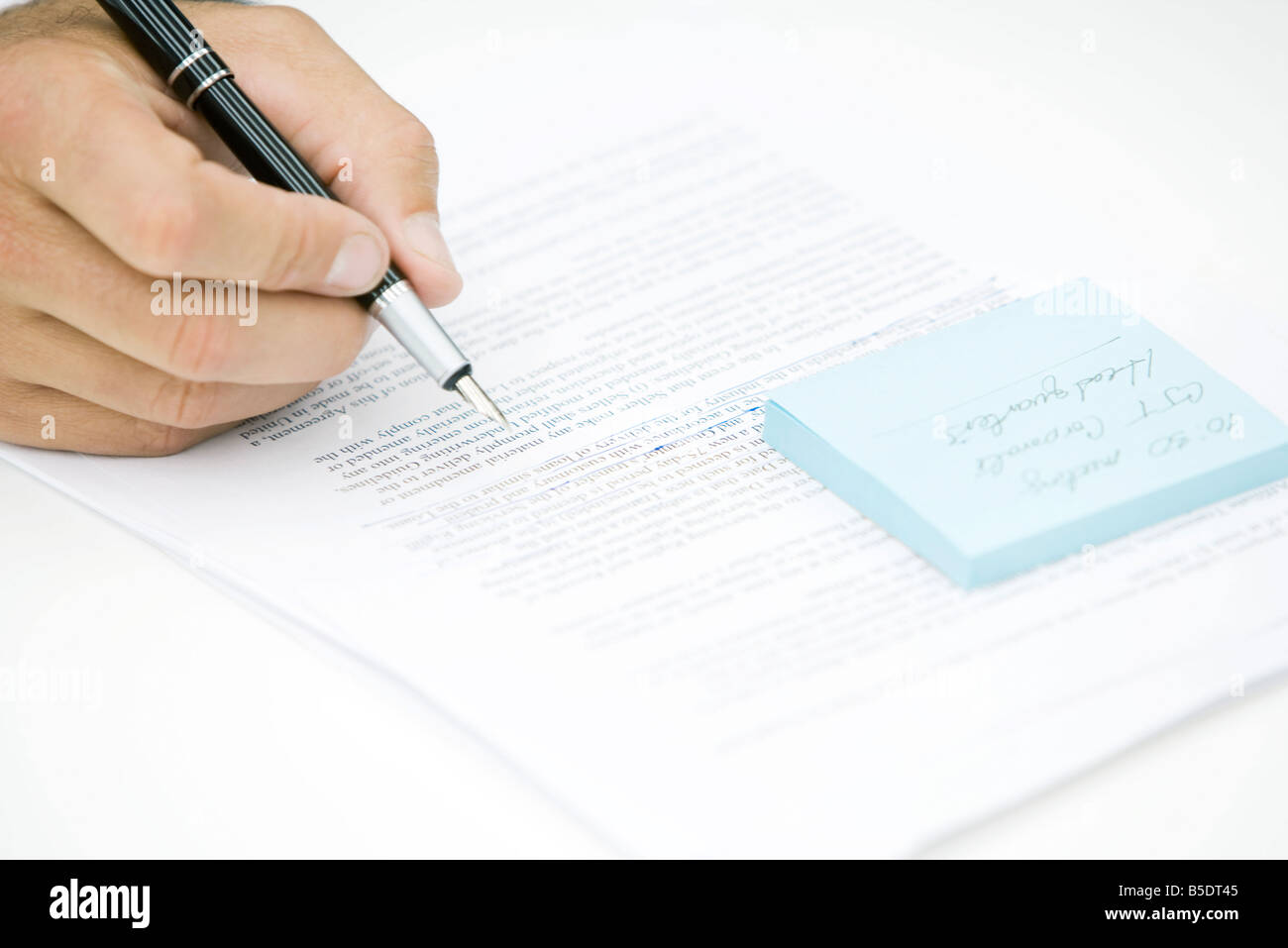 Hand holding pen, editing document - Stock Image