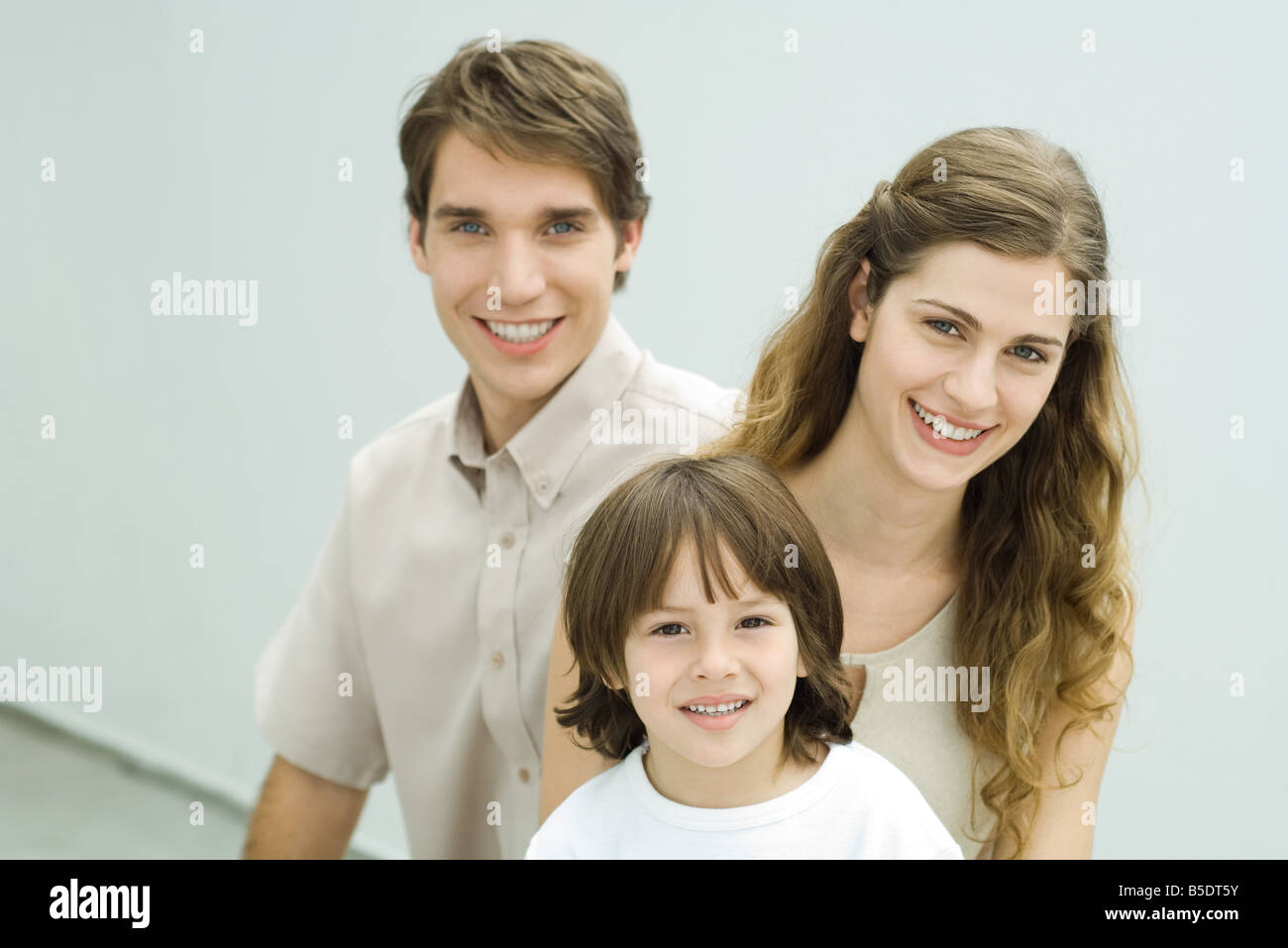 Family smiling at camera, portrait - Stock Image