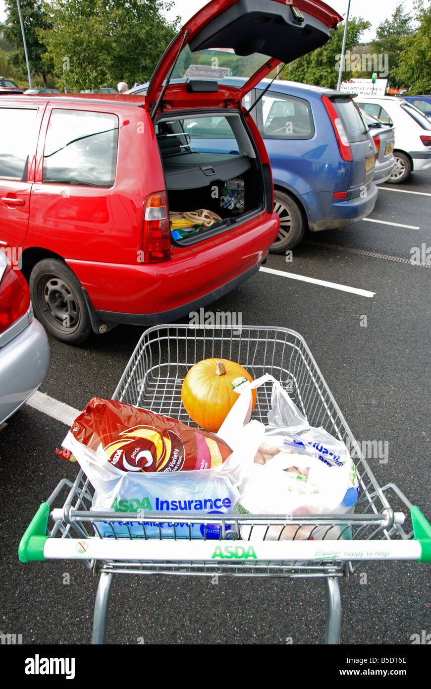 a trolley full of shopping about to be loaded into the boot of a car - Stock Image
