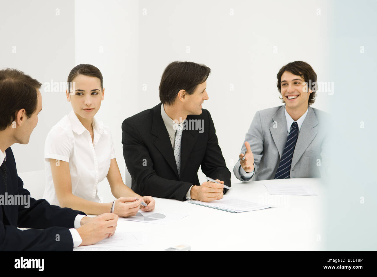 Business associates sitting around conference table, looking at each other, smiling - Stock Image