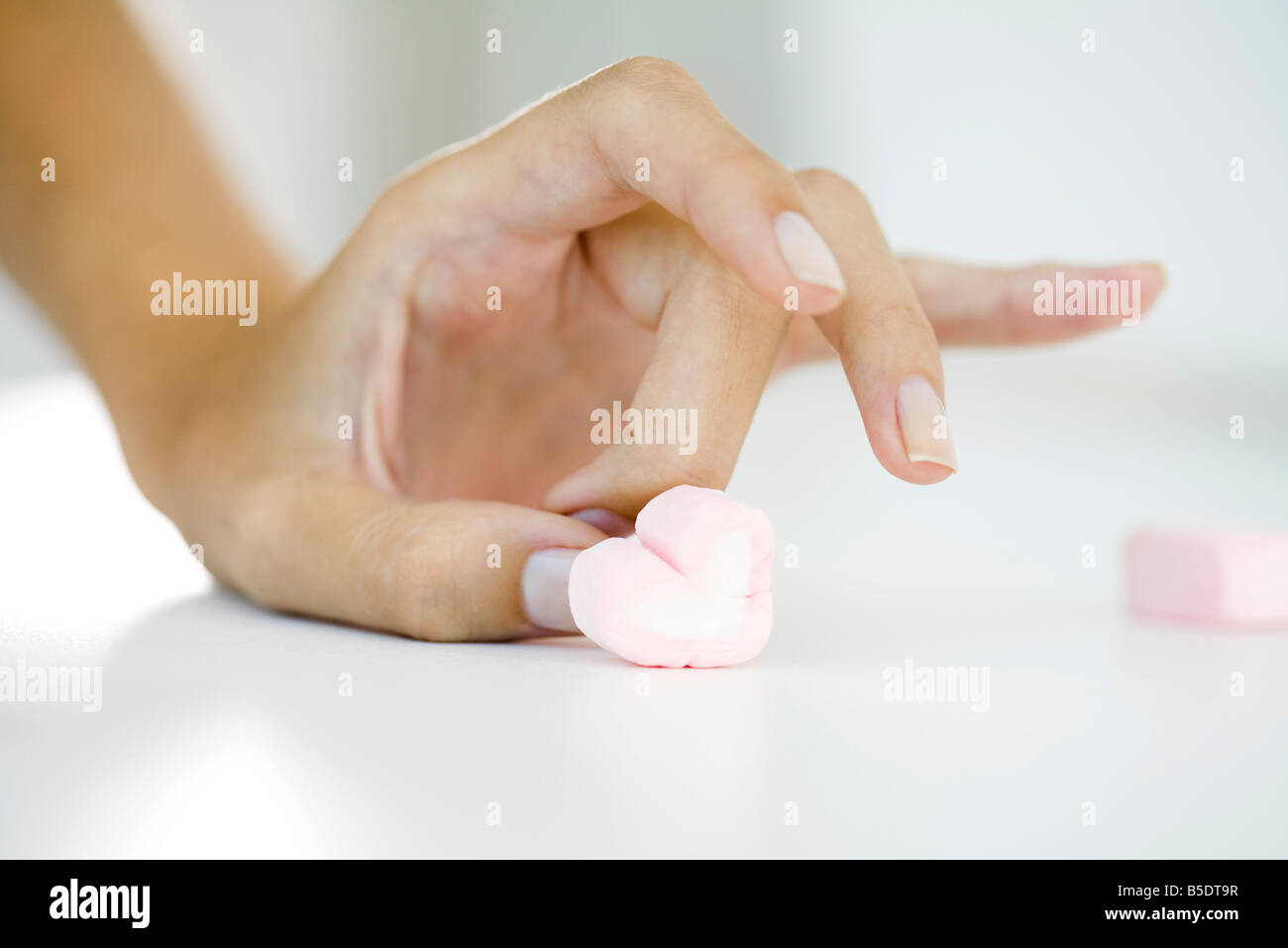 Woman's hand flicking marshmallow heart - Stock Image