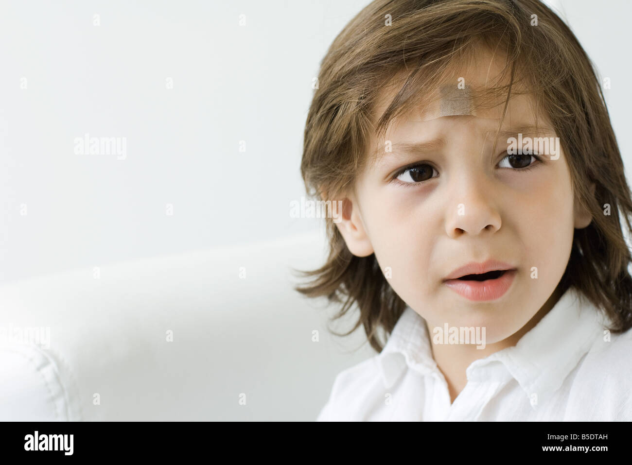 Little boy with adhesive bandage on his forehead, looking away and furrowing brow - Stock Image