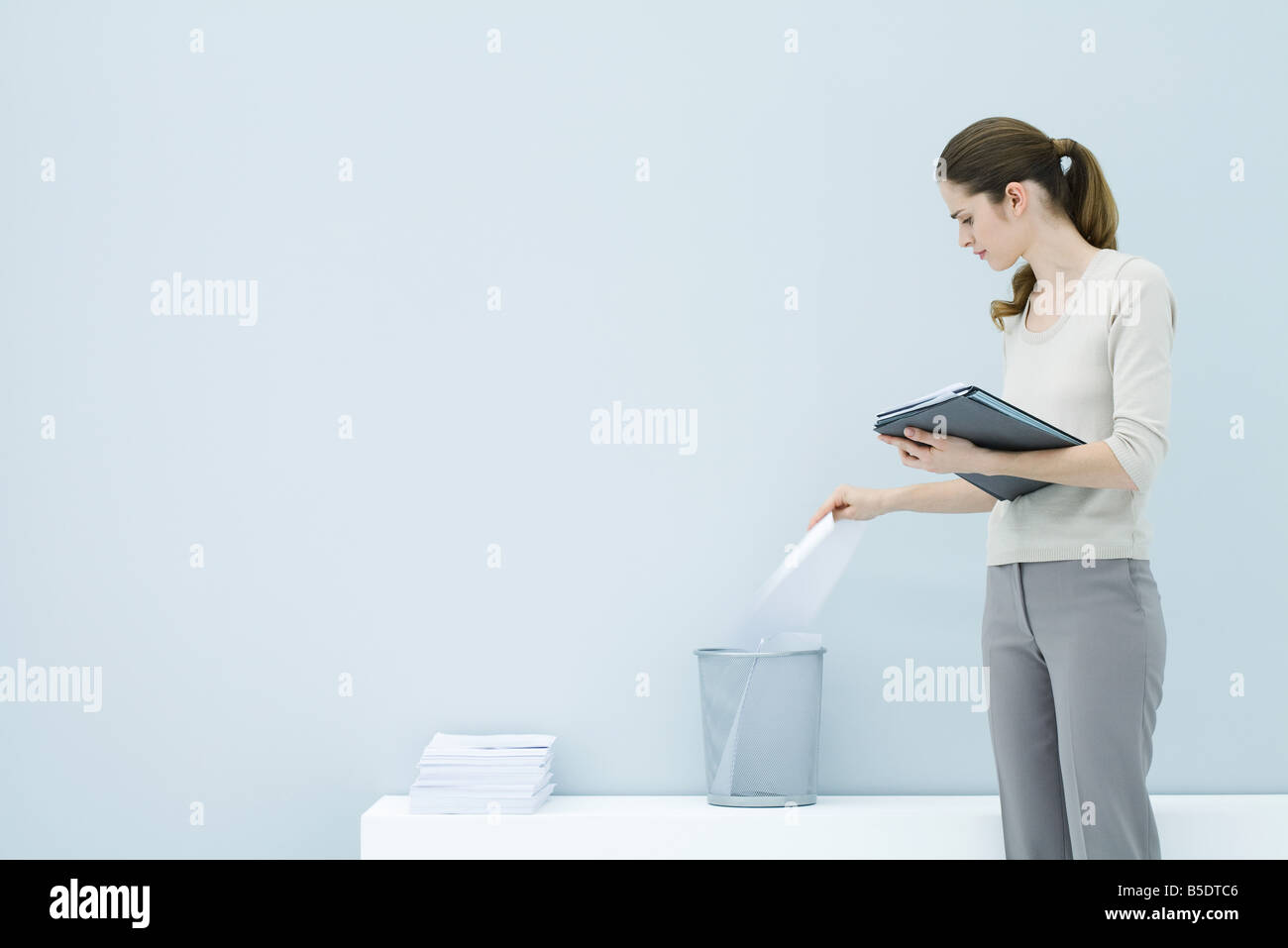 Professional woman throwing away document, holding folder - Stock Image