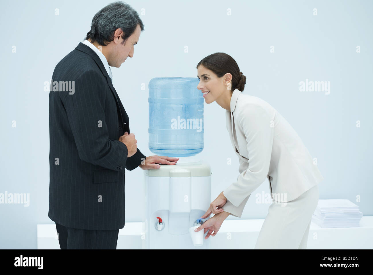 Two professionals chatting beside water cooler, woman filling disposable cup Stock Photo