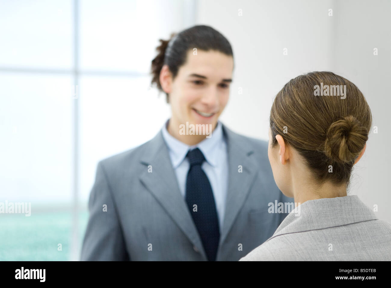 Professional young man facing female colleague, smiling - Stock Image