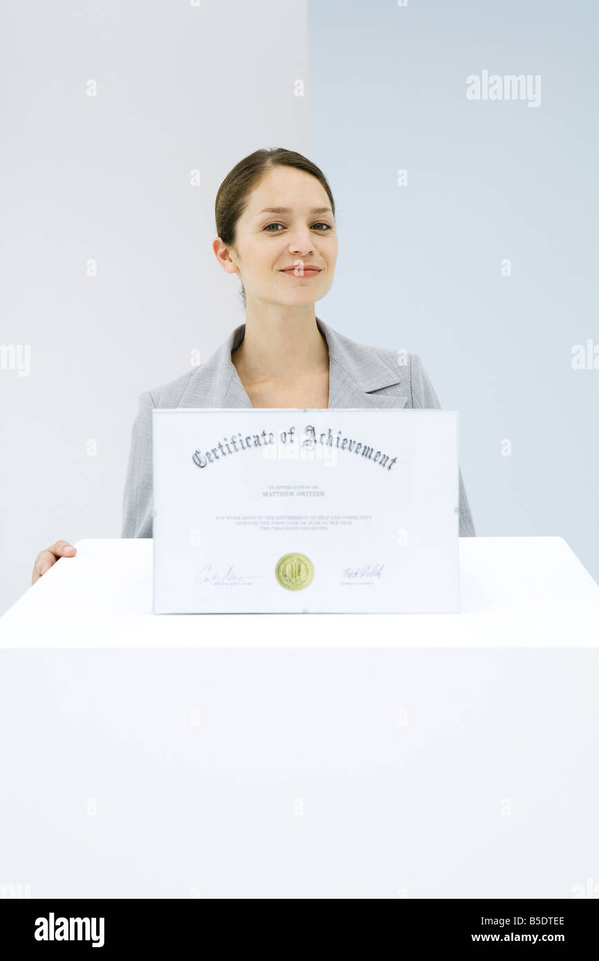 Woman standing behind pedestal with certificate on top of it, smiling at camera - Stock Image