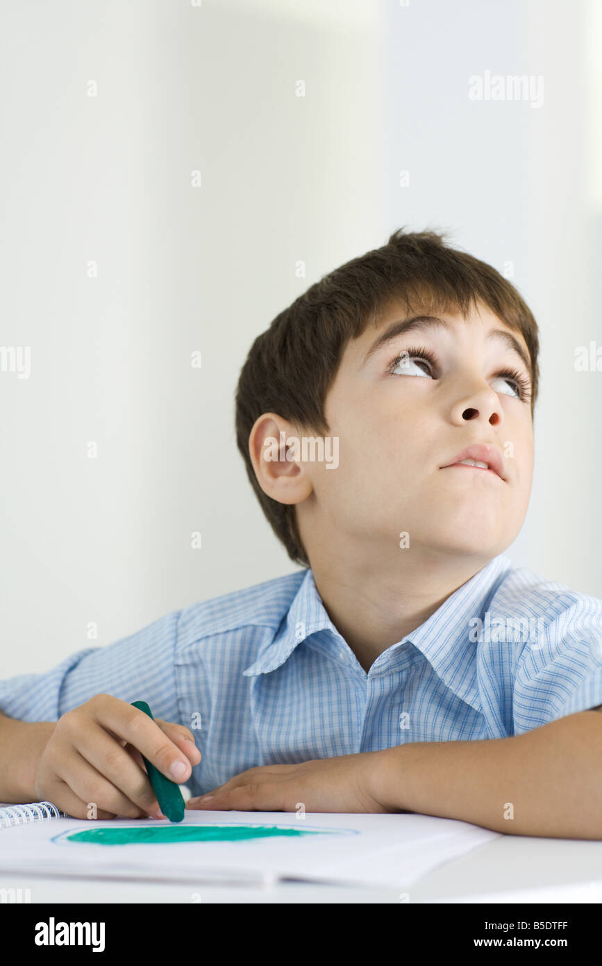 Boy coloring with crayon, looking up - Stock Image