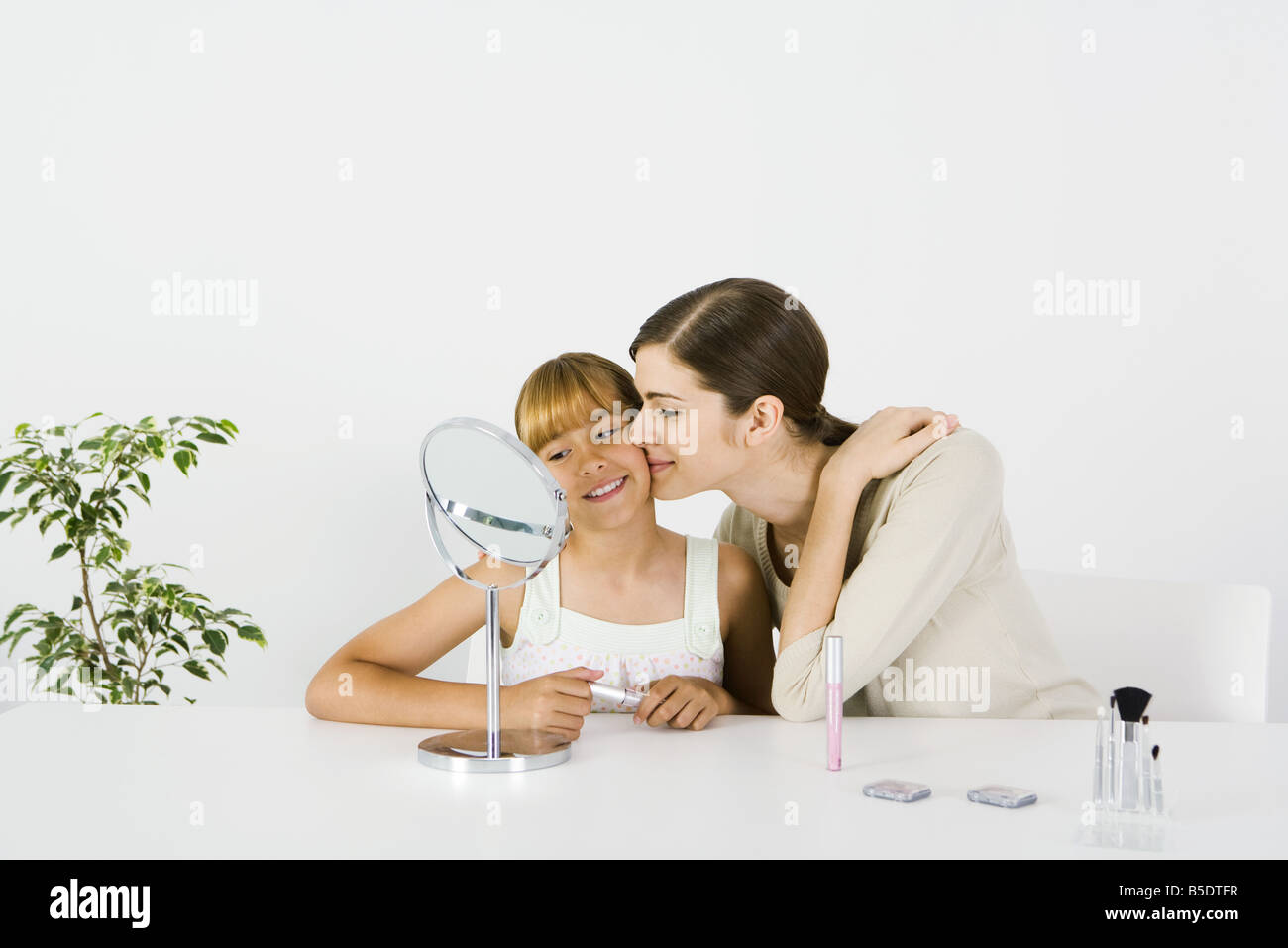 Young woman and preteen sister sitting in front of mirror, older sister kissing younger sister's cheek Stock Photo