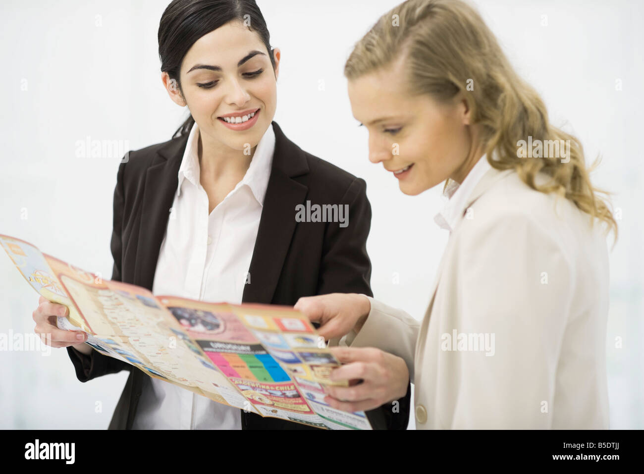 Two women looking at travel brochure together - Stock Image