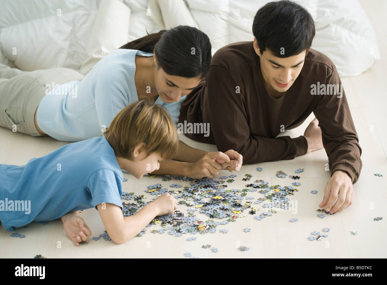 Family lying on floor, putting together jigsaw puzzle - Stock Image